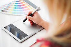Graphic designer working on a digital tablet in the background with pantone palette